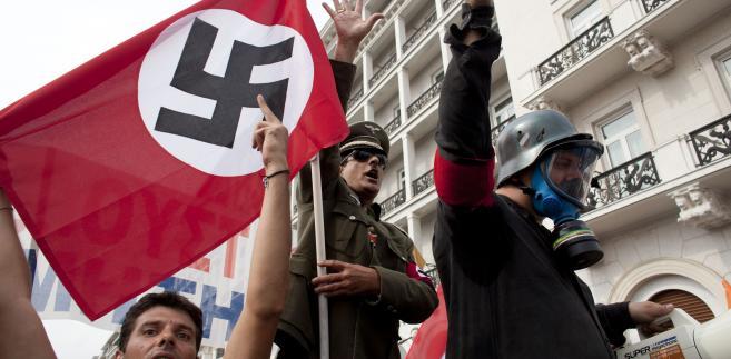 """FAZ: kanclerz """"jeszcze nigdzie nie została przyjęta tak, jak w Grecji: z wojskowymi honorami i symbolami swastyki"""". (na zdjęciu protestujący Grecy podczas wizyty Angeli Merkel)."""